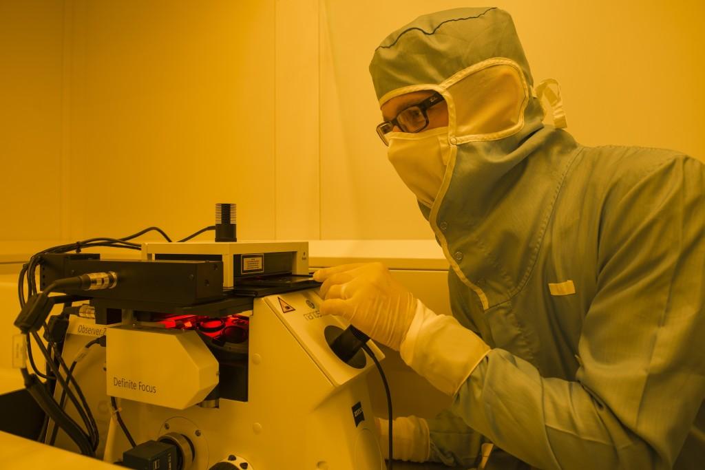 Der PSI-Forscher Robert Kirchner an dem Lasergerät, mit dem Modelle des Matterhorns hergestellt wurden, die jeweils nur rund sieben Hundertstel Millimeter gross waren. Der Forscher trägt einen Schutzanzug, der das Gerät und die Proben vor Staub und Haaren schützt. Der Raum ist gelb ausgeleuchtet, weil die Modelle aus lichtempfindlichem Material hergestellt werden, das von dem gelben Licht aber nicht beeinflusst wird. (Foto: Paul Scherrer Institut/Mahir Dzambegovic)