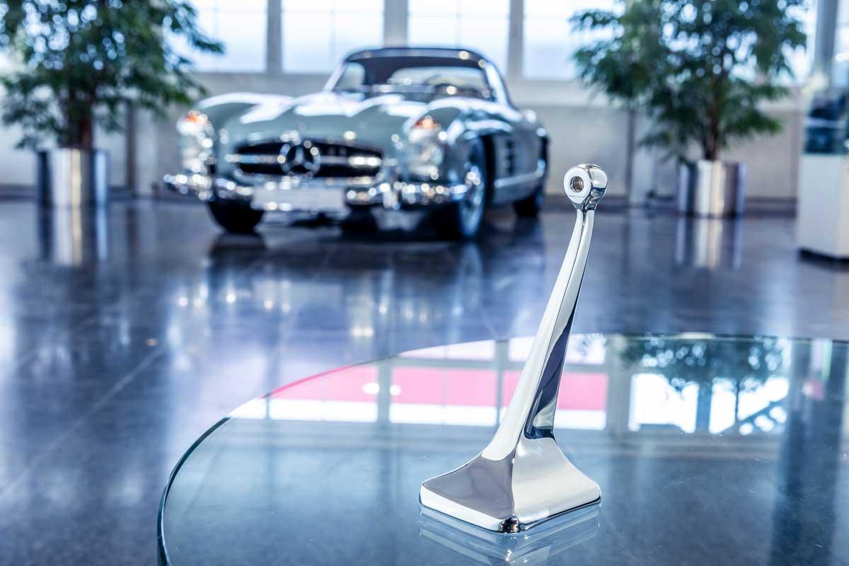 Innenspiegelfuß der Mercedes-Benz Baureihe 198 (Coupé und Roadster). Er ist als Original-Ersatzteil wieder erhältlich und kann bei jedem Mercedes-Benz Partner über das Classic Center bezogen werden. Der Spiegelfuß wird mithilfe des 3D-Drucks aus einer Aluminiumlegierung hergestellt.